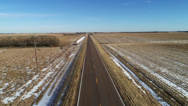 the scenic panoramic aerial view of the small highway between the harvested fields in the country farmland - kansas stock videos & royalty-free footage