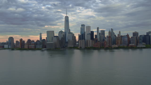 夕暮れのジャージーシティからハドソン川を渡るマンハッタンの風光明媚な景色。複雑な映画の前方と上昇カメラの動きを持つ空中映像。 - 連続するイメージ点の映像素材/bロール