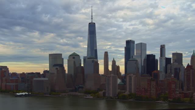 日没直前の夜遅くにジャージーシティからハドソン川を渡るマンハッタンの風光明媚な景色。パンカメラの動きを伴う空中映像。 - 連続するイメージ点の映像素材/bロール