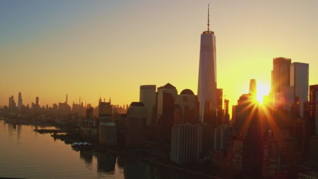 日の出時にジャージーシティからハドソン川を渡るマンハッタンの風光明媚な景色。映画の広い軌道カメラの動きを持つ空中映像。 - 連続するイメージ点の映像素材/bロール