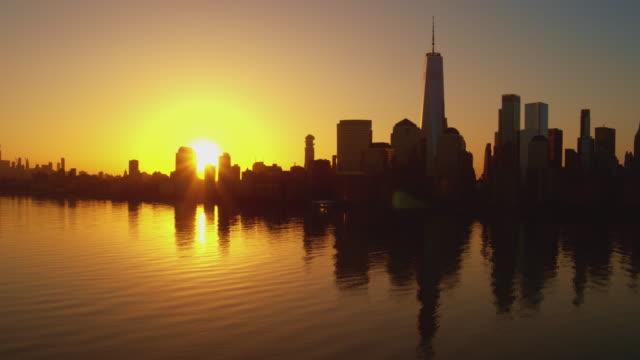 日の出時にジャージーシティからハドソン川を渡るマンハッタンの風光明媚な景色。映画のパノラマカメラモーションを持つ空中映像。 - 連続するイメージ点の映像素材/bロール