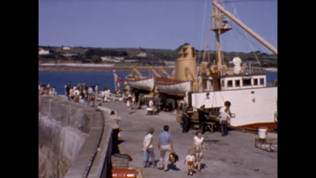 the scillonian ferry at port in penzance cornwall england / passengers at the dockside overview of ship | crew loading the ship with items and... - harold wilson stock-videos und b-roll-filmmaterial