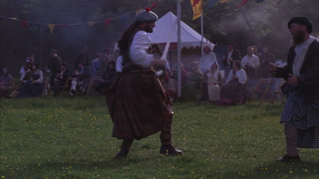 The Scottish Highland games include sword fighting and a bagpiper band.