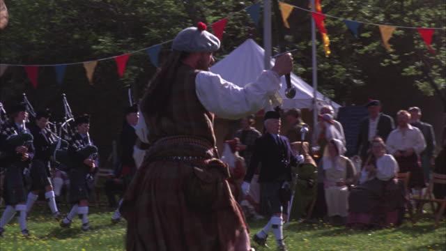 the scottish highland games include sword fighting and a bagpiper band. - gå tillsammans bildbanksvideor och videomaterial från bakom kulisserna