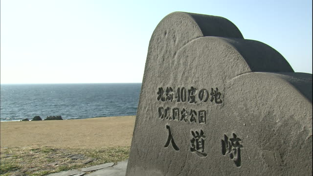 the sea of japan ripples beyond a monument for the 40th parallel north on cape nyudo. - 秋田県点の映像素材/bロール