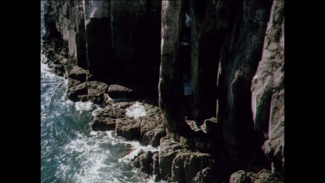 vidéos et rushes de tu the sea swells up against rock cliffs of a large plain / uk - rock face