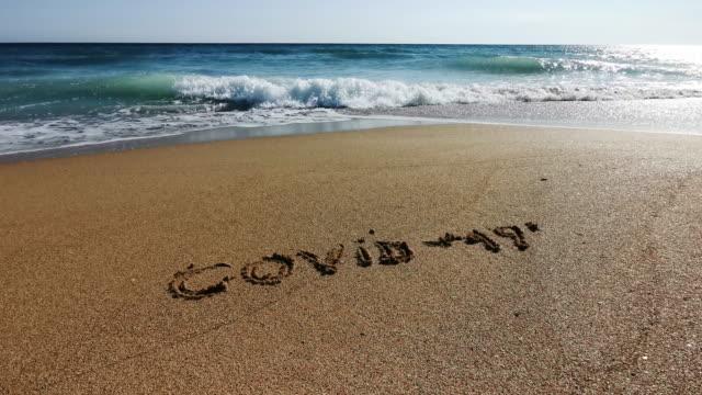 pov der meereswellen, die die covid-19-inschrift auf der goldenen sandküste auswaschen. konzepte und symbolik. - the end stock-videos und b-roll-filmmaterial