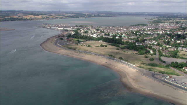 the sea wraps around a beach peninsula in england. - peninsula stock videos and b-roll footage