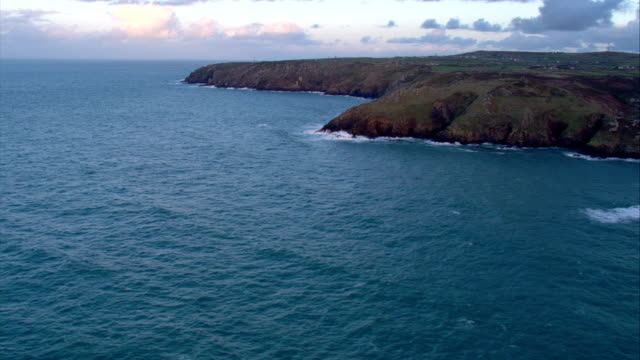 The sea wraps around the curves of an uneven coastline in Scotland. Available in HD.