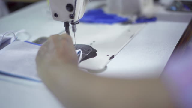 the seamstress is sewing the mask - cucire video stock e b–roll
