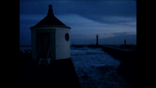 tu the seaside at dusk with views of the pier, lighthouses and the surrounding cliffs / whitby, united kingdom - peter greenaway stock videos & royalty-free footage