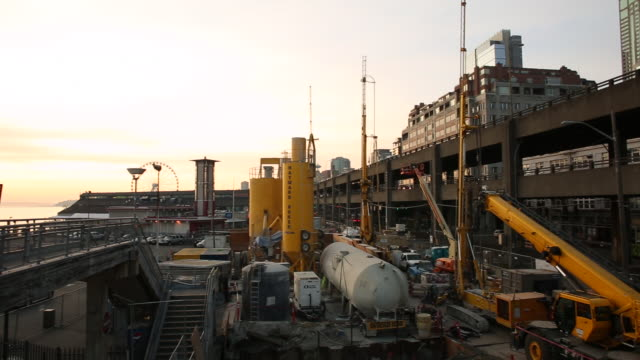 The Seattle waterfront with construction vehicles at sunset.