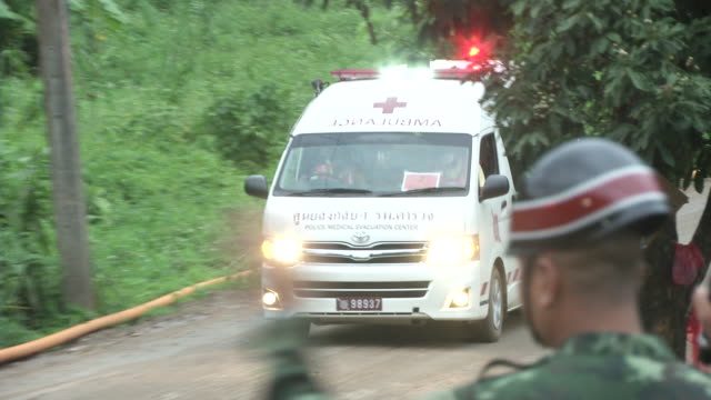 the second ambulance leaves the tham luang cave area after divers evacuated some of the boys among a group of 13 trapped in a flooded cave in khun... - chiang rai province stock videos and b-roll footage