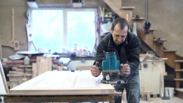 the senior 65-years-old craftsman working with the electric hand milling machine. woodworks on the small furniture factory. - 65 69 years stock videos & royalty-free footage