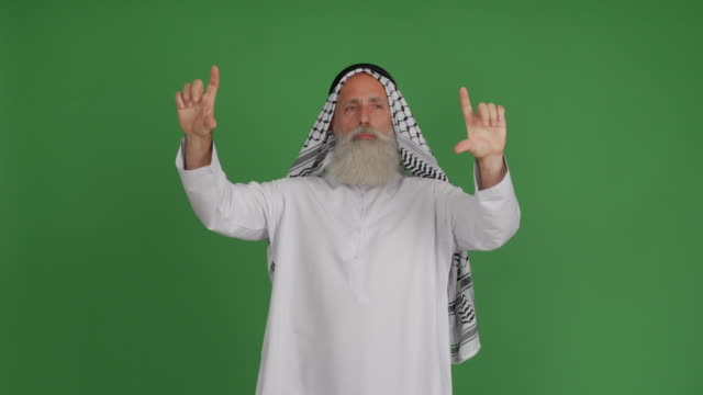 the senior arab manages his hands in something in virtual space on a green background - kharkov stock videos & royalty-free footage