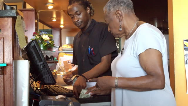 The senior black active 77-years-old businesswoman counting money together with the bartender on the cash register in the small local restaurant