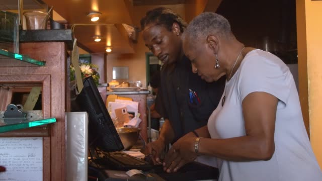 the senior black active 77-years-old businesswoman counting money together with the bartender on the cash register in the small local restaurant - counting stock videos & royalty-free footage