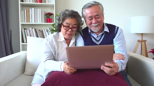シニアカップルはノートを開き、家族とビデオ通話を使用しています。 - ズーム点の映像素材/bロール