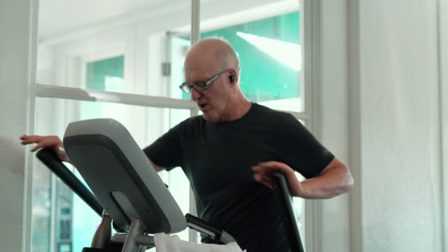 the senior man doing fitness workout in the gym, using the elliptical trainer machine. - treadmill stock videos & royalty-free footage