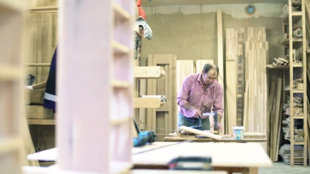 the senior man, manual worker - sashman, sticks together wooden details in a finished product using clamps at the small furniture factory. - 65 69 years stock videos & royalty-free footage