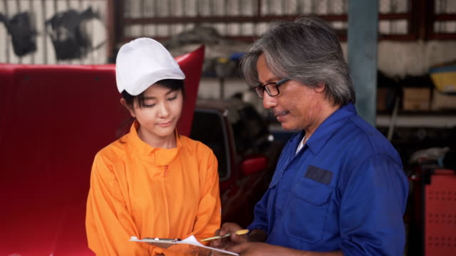 The senior mechanic and Asian young female car mechanic smiling