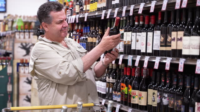 the senior positive latino man with a shopping cart shopping in a liquor store, purchasing a vine. - wine stock videos and b-roll footage