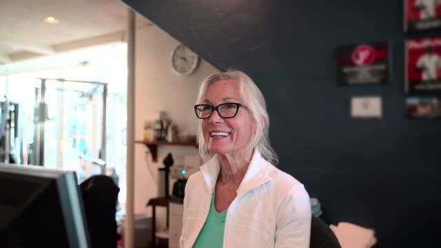 stockvideo's en b-roll-footage met de senior glimlachende vrouw draagt brillen werken bij de receptie - secretaris