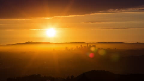 the setting sun over the los angeles skyline - sunset stock videos & royalty-free footage