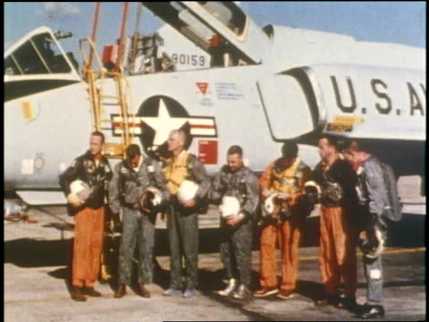 the seven mercury astronauts in flight suits stand in line next to a fighter jet. - alan b. shepard jr stock videos & royalty-free footage