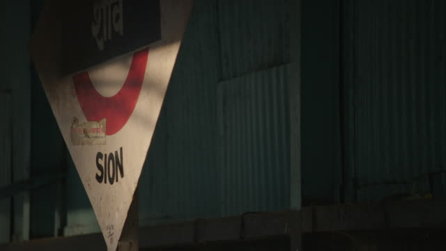 the shadow of a departing train passes across a sign indicating sion station in mumbai, maharashtra, india. - simbolo informazioni video stock e b–roll