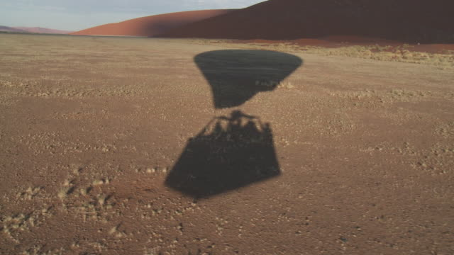 the shadow of a hot air balloon drifts across the desert in namibia. - balloon stock videos and b-roll footage