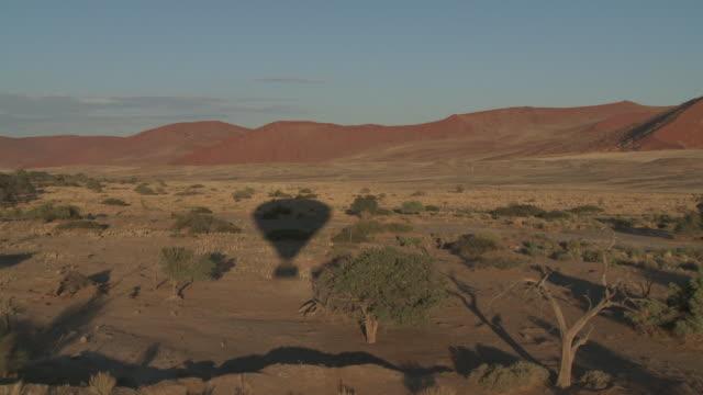 The shadow of a hot air balloon drifts across the Namibian desert.