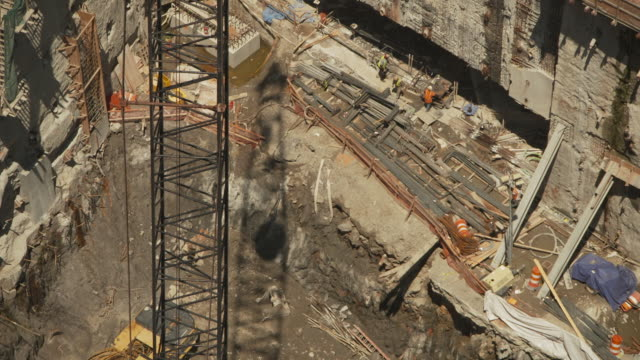 the shadow of a large piece of machinery moves across a pit in the ground during construction of the new world trade center, summer 2011, manhattan, new york city, usa. - rebuilding stock videos & royalty-free footage