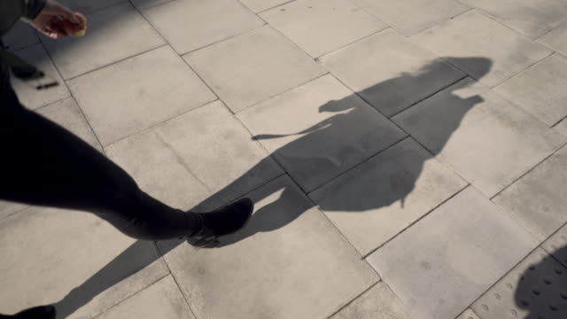 The shadow of a woman walking, with a bag, apple and phone.