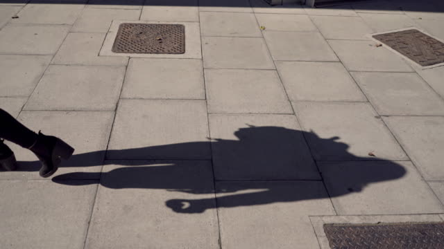 vídeos de stock e filmes b-roll de the shadow of a woman walking, with a bag, apple and phone. - parte inferior
