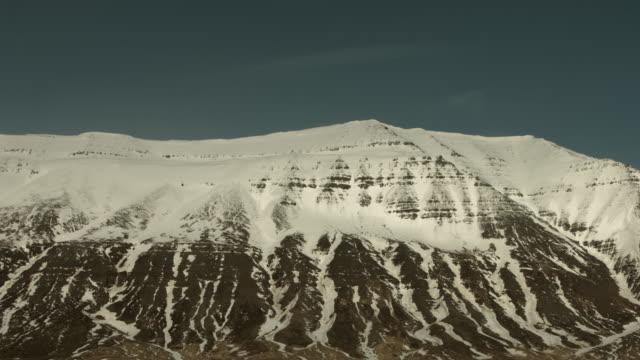vídeos de stock, filmes e b-roll de the shadows of clouds drift across a snow covered mountain. - países nórdicos