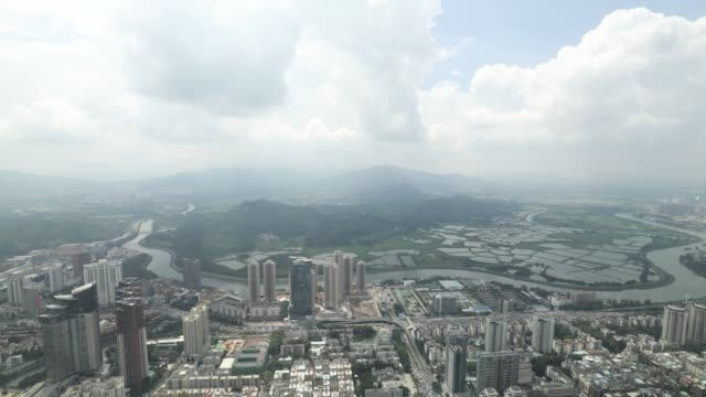 The Sham Chun river marking the border between residential and commercial buildings in mainland China foreground and farmland in Hong Kong is seen...