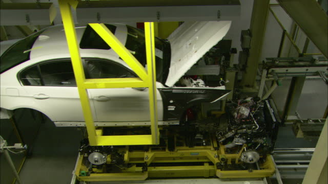 vidéos et rushes de the shell of a car and the chassis assembly come together as two lifts raise and lower in an automobile factory. - usine automobile