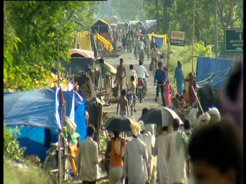 the shelters of people displaced by flooding line a road in the state of bihar india - emergency shelter stock videos & royalty-free footage