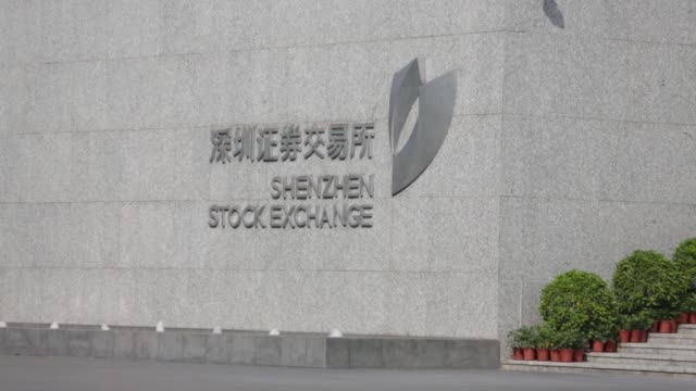 the shenzhen stock exchange flag flies in front of a chinese national flag outside the shenzhen stock exchange building in shenzhen china on... - brühe stock-videos und b-roll-filmmaterial
