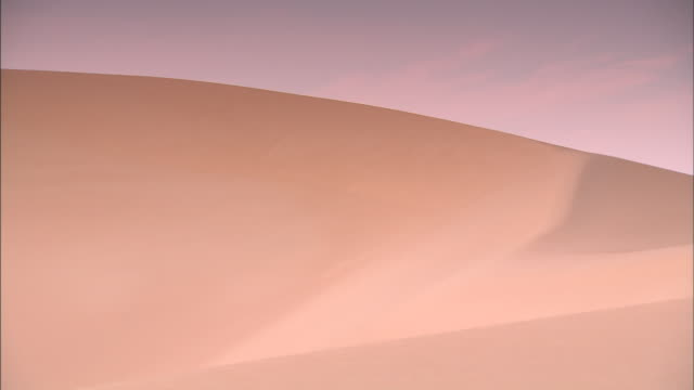 the shifting sands have contoured a sand dune into a ridge and smooth side. - sand dune stock videos & royalty-free footage