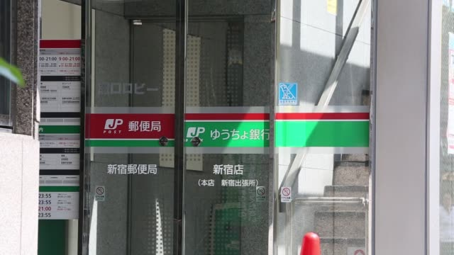 the shinjuku post office, operated by japan post holdings co., stands in tokyo, japan, on monday, sept. 11 a customer enters the shinjuku post... - mail点の映像素材/bロール