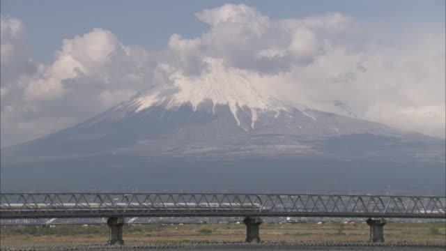 vidéos et rushes de the shinkansen travels over a bridge in front of mount fuji. - préfecture de yamanashi
