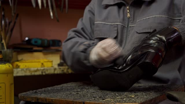 the shoemaker making a hole and putting glue on heel of a woman's leather shoes - protective glove stock videos & royalty-free footage