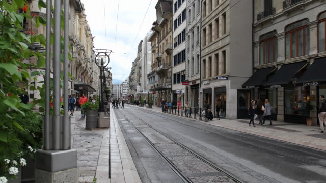 the shopping street rue de la croix d'or in downtown geneva in switzerland passersby can be seen and in the middle of the street run tram rails - dor stock videos & royalty-free footage