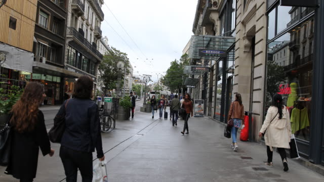 the shopping street rue de la croix d'or in downtown geneva in switzerland passersby can be seen and on the left run tram rails - dor stock videos & royalty-free footage