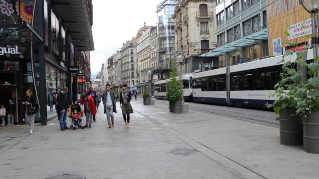 vídeos y material grabado en eventos de stock de the shopping street rue de la croix d'or in downtown geneva in switzerland passersby can be seen and a tram passes by on the right side - vía de tranvía