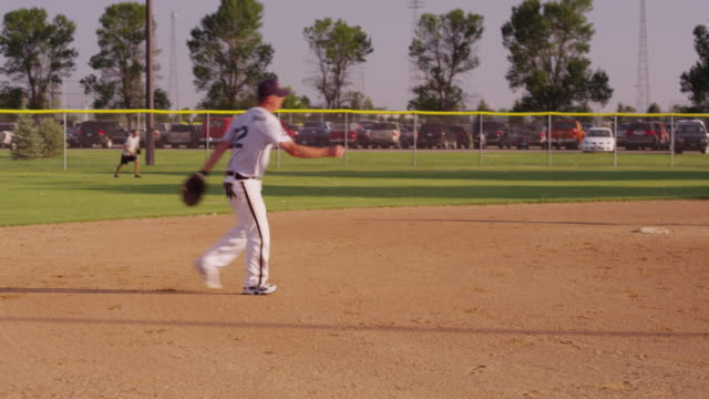 the short stop catches a ball, throws it to the pitcher, end of inning at a men's league softball game. - inning stock videos & royalty-free footage