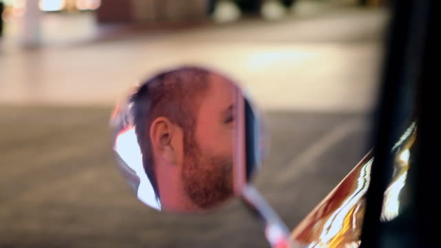 vídeos de stock, filmes e b-roll de the side view mirror of a vintage car reflects the face of a smiling driver on las vegas boulevard at night. - só um homem jovem