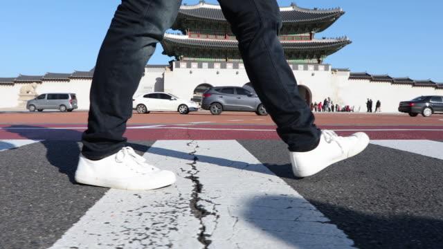 vidéos et rushes de the side view of the man's leg and walking on the crossroad near the gwanghwamun gate (entrance of gyeongbokgung palace) - vue latérale